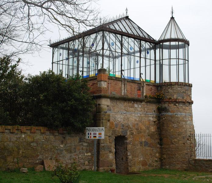 Une tour surmontée d'une serre avec vingt et un escaliers qui descendent au jardin du domaine où se situe une autre serre, soit deux serres