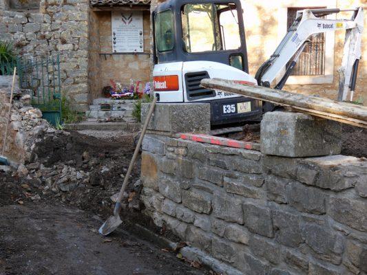 Muret démoli et pelleteuse dans le jardin du calvaire